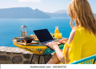 Woman working with laptop computer while having breakfast