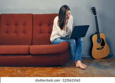 Woman working with laptop on sofa.