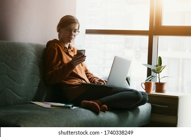 Woman working with laptop and phone at home. Comfortable workplace with coffee on couch. Stay at home campaign.