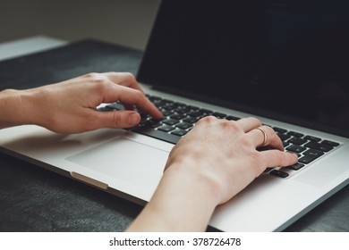 Woman working with laptop placed on the black desk