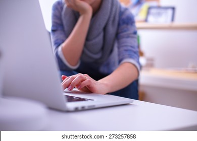 Woman working with a laptop sitting at the desk