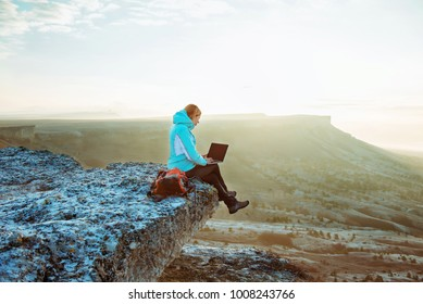 woman working with laptop sitting on the rocky mountain