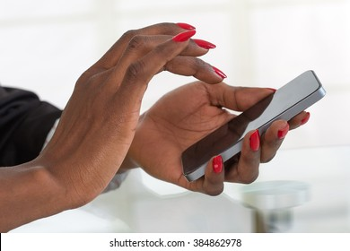 woman working with a mobile phone above business documents
