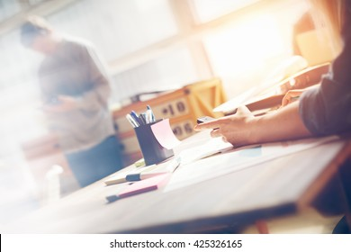 Woman working with mobile phone in office. Paperwork on the table, open space. Sun glare, film effect and blurry background