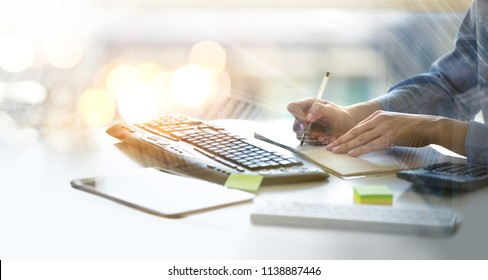 Woman working in the office against of the window, lit up with sunlights. Close up  hands holding pen working on calculator, tablet, keyboard, calculating business data.