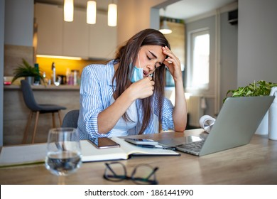 Woman working in the office and having difficulties breathing with face mask, she is pulling the mask down. The woman had to remove the mask to breathe after having to wear it for a long time