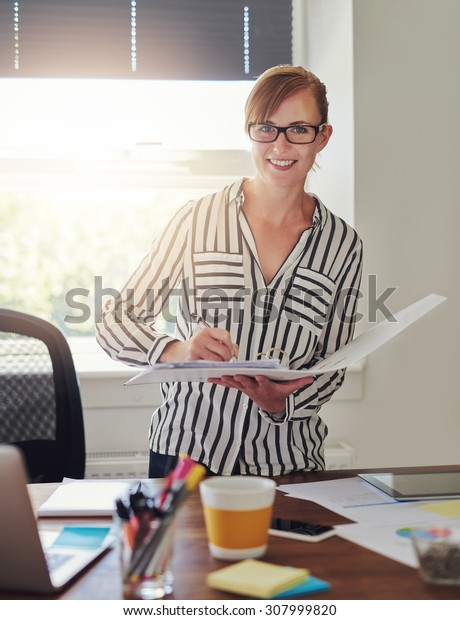 Woman working at office holding papers