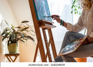 Woman working on abstract painting at cozy workplace with green plants. Painter in her studio. Art and craft concept from modern home interior