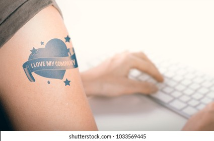 Woman working on a computer with close up on a tatoo with the text i love my company.  Concept of employee advocacy and engagement.