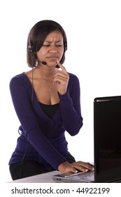 A woman working on her computer with a serious expression on her face with her finger on her lip thinking.