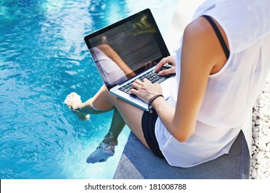 Woman working on her laptop computer sitting at poolside