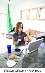 Woman working on her laptop and eating breakfast at home.
