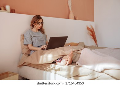 Woman working on a laptop in bed. Working from home. Quarantine.