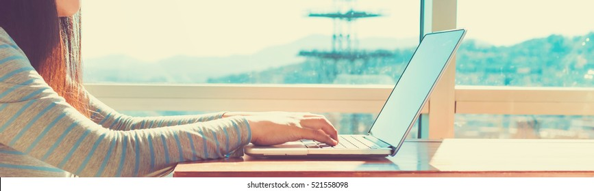 Woman working on a laptop in brightly lit room
