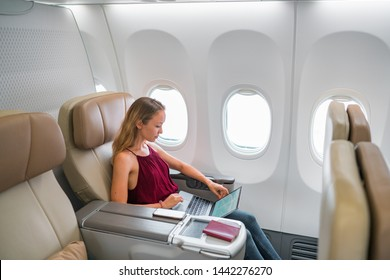 Woman working on laptop in business class