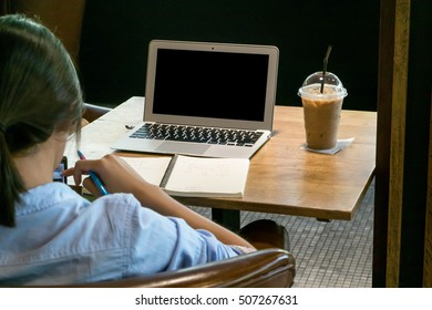 Woman working on laptop in coffee shop with cup of coffee, selective focus on laptop, blurred foreground