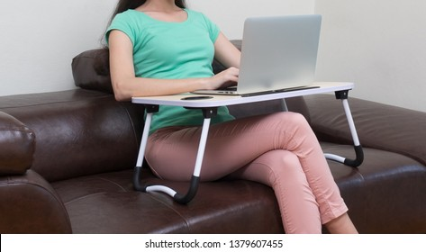woman working on laptop computer on portable table at home