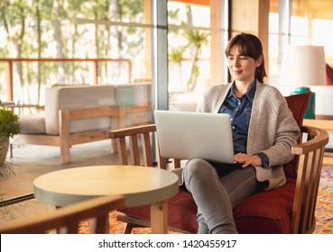 Woman working on a laptop on a cozy space