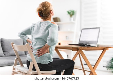 Woman working on a laptop and having back, hip, spine pain.
