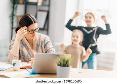 Woman working on a laptop. Noisy children and remote work from home.