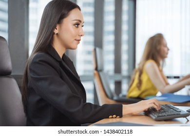 Woman working on laptop at office while , businesswoman portrait