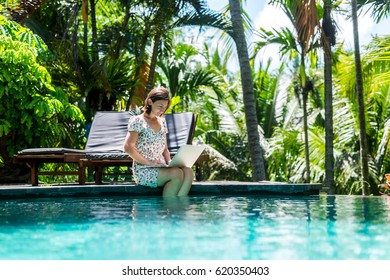 Woman working on laptop sitting by the pool outdoor. Tropical nature. The modern concept of remote work at home, freelance business, blogging, digital nomad.