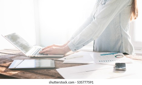 Woman working on a laptop and tablet pc indoor on a wooden standing desk