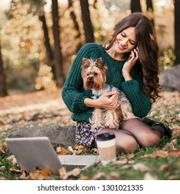 Woman working on laptop and talking on the phone in the park with dog in her arms.