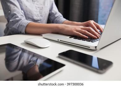 woman working on laptop on wooden desk in office