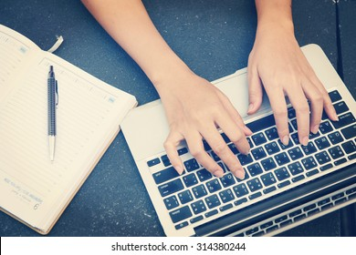 Woman working on laptop and writing, top view