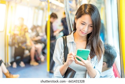 Woman working on mobile phone inside train compartment