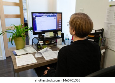 Woman working on PC at computer desk. A view from behind a female employee sitting at an office workstation, looking towards a computer monitor with open software. Worker studies on office task.