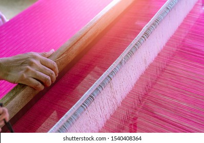 Woman working on weaving machine for weave handmade fabric. Textile weaving. Weaving using traditional hand weaving loom on the long cotton strands. Textile production in Thailand. Asian culture.