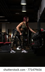 Woman Working Out Back In A Gym With Dumbbells