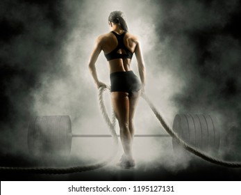 Woman working out with battle ropes at gym