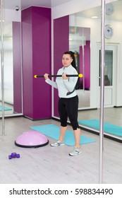 Woman working out with body bar in the fitness studio