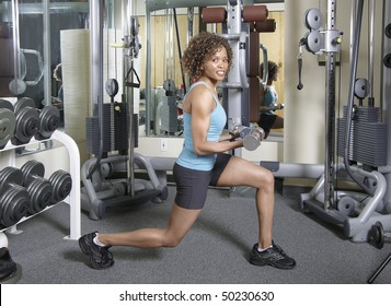 Woman working out doing lunges and curls with weights in a gym