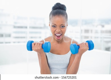 Woman working out with dumbbells at home