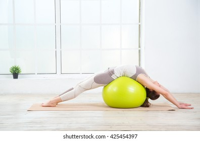 Woman working out with exercise ball in gym. Pilates woman doing exercises in the gym workout room with fitness ball. Fitness woman doing exercises for muscle press with abs swiss ball.