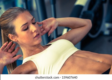 Woman working out in fitness - Active girl professional fitness cometrtitor doing abs aexercise in gym club