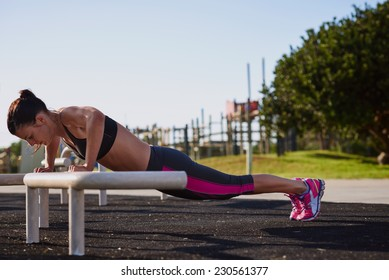 woman working out in gym doing pushups on equipment outdoors having fun