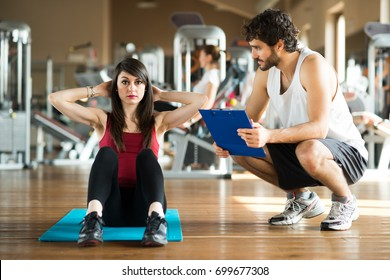 Woman working out in a gym with her personal trainer