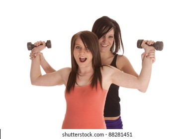 A woman working out her arms with her trainer pushing her.