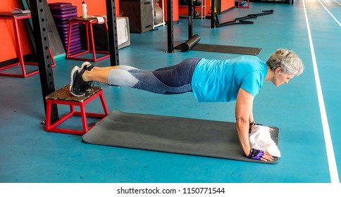 woman working out her pectoral muscles; woman doing pushups; woman doing incline pull-ups