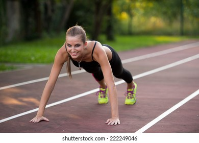 Woman working out on athlete track on summer afternoon