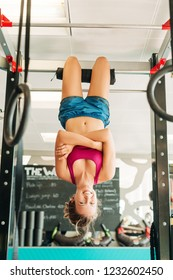 Woman working out on cross bars in a gym, hanging upside down