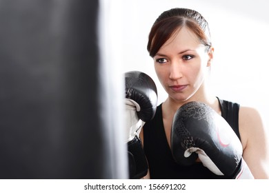 Woman working out on punch bag in gym
