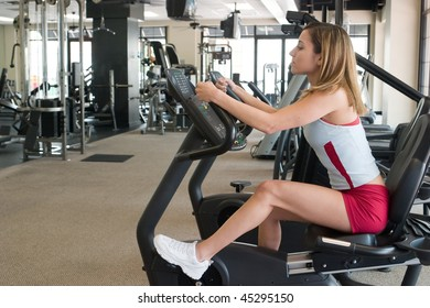Woman working out on a stationary cycle machine in a fitness club.