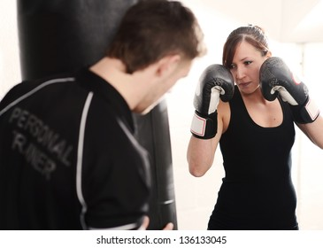 Woman working out with personal trainer on punch bag in gym