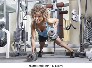 Woman working out with weights in a gym